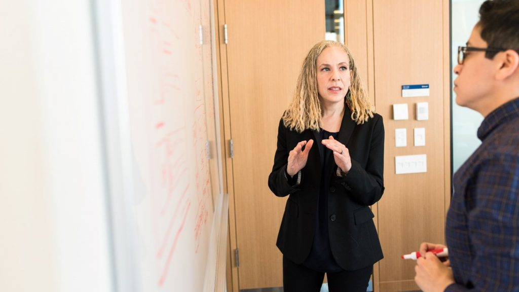 woman wearing suit in front of white board