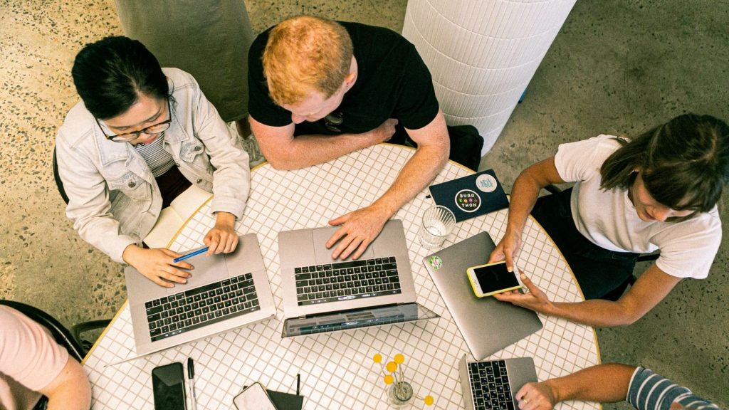 three people at a startup working on branding together on their laptops