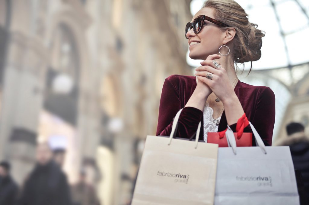 woman holding two white and beige shopping paper bags