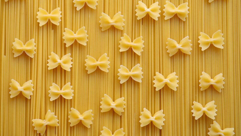 dry bowtie pasta pieces on top of a background of dry spaghetti