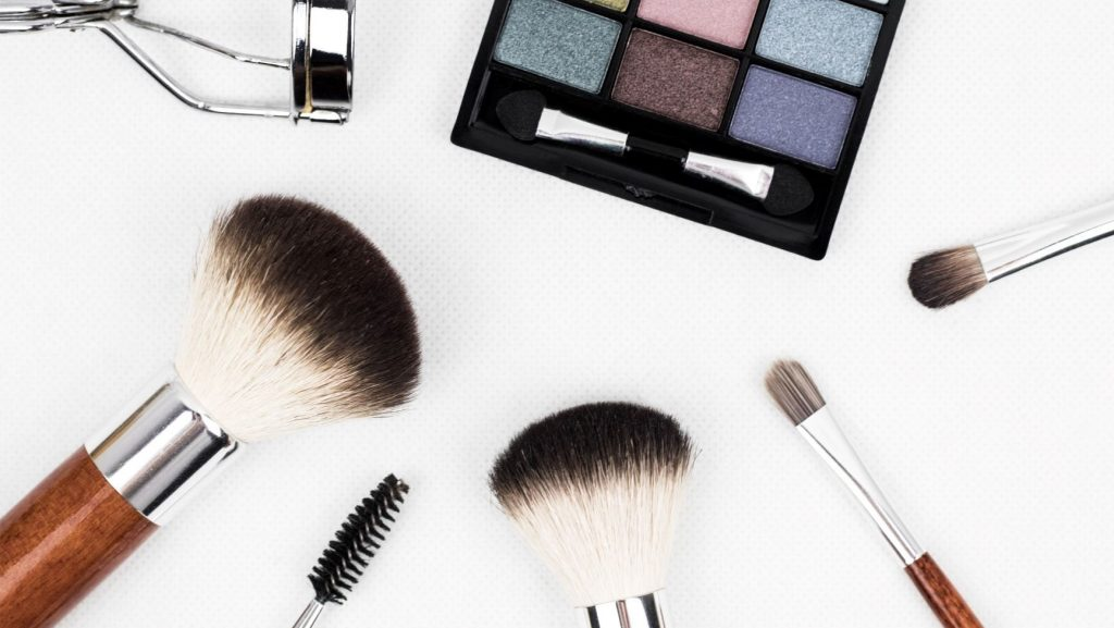 make up brushes and cosmetics on white background