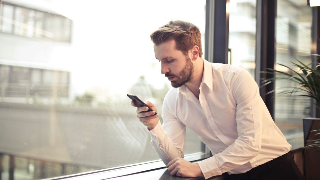 business man looking at phone in front of window