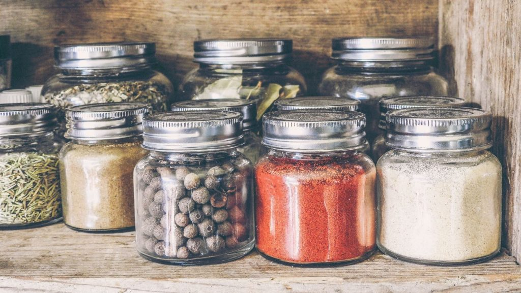 glass jars with spices on a shelf with no branding or packaging design