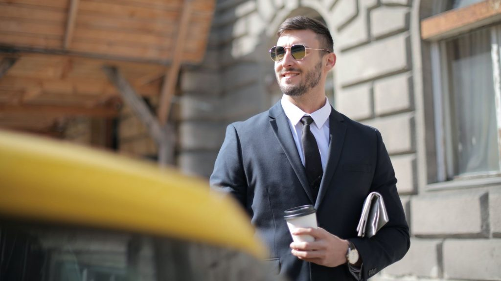 business man wearing a suit and holding coffee