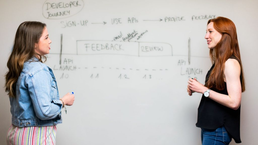 two women standing in front of a white board