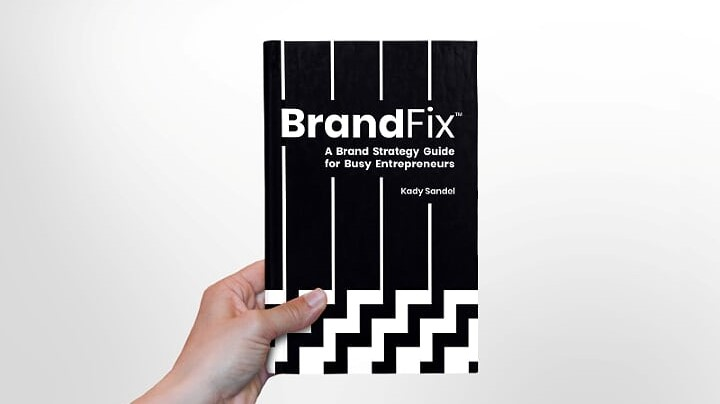 A hand holding a paperback copy of the book BrandFix by Kady Sandel