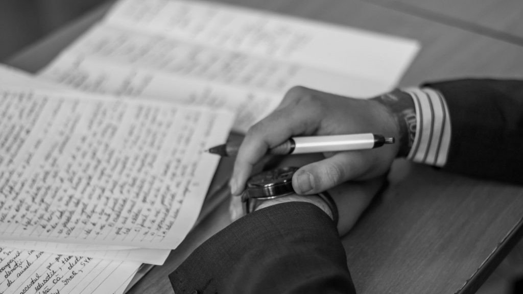 person holding a pen and writing words on the page