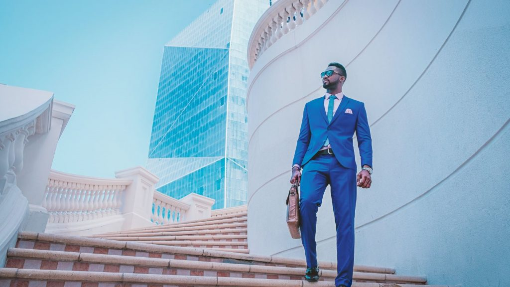 man in blue suit walking down stairs