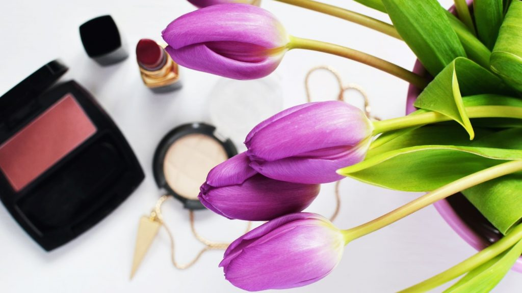 natural cosmetics next to purple tulips