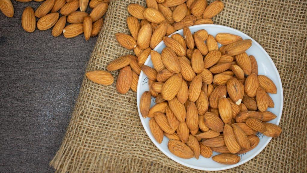brown almonds in white bowl