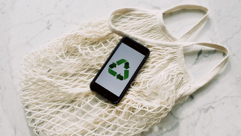cell phone with recycling symbol lying on reusable bag