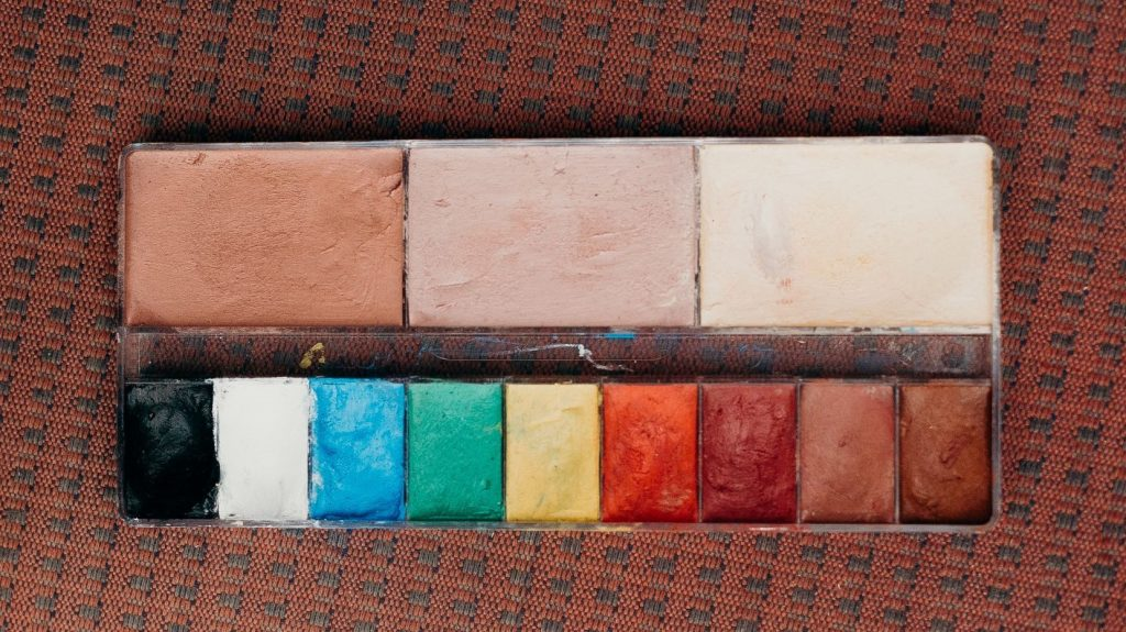 palette of paints on a red carpet
