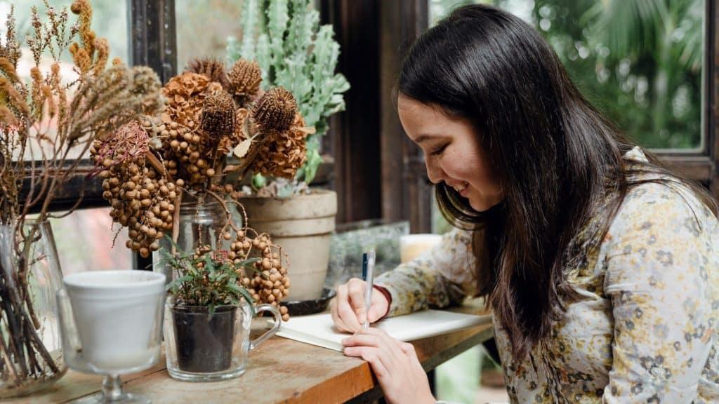woman writing business plan next to plants
