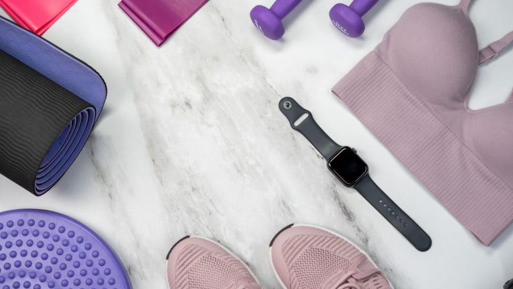 pink sports bra, black smart watch, purple dumbbells