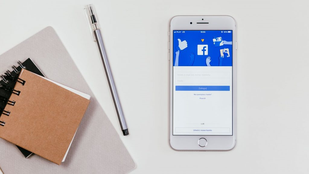 iphone with facebook on the screen next to notebooks