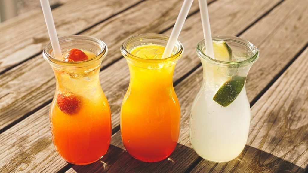 three healthy fruit juices in glasses