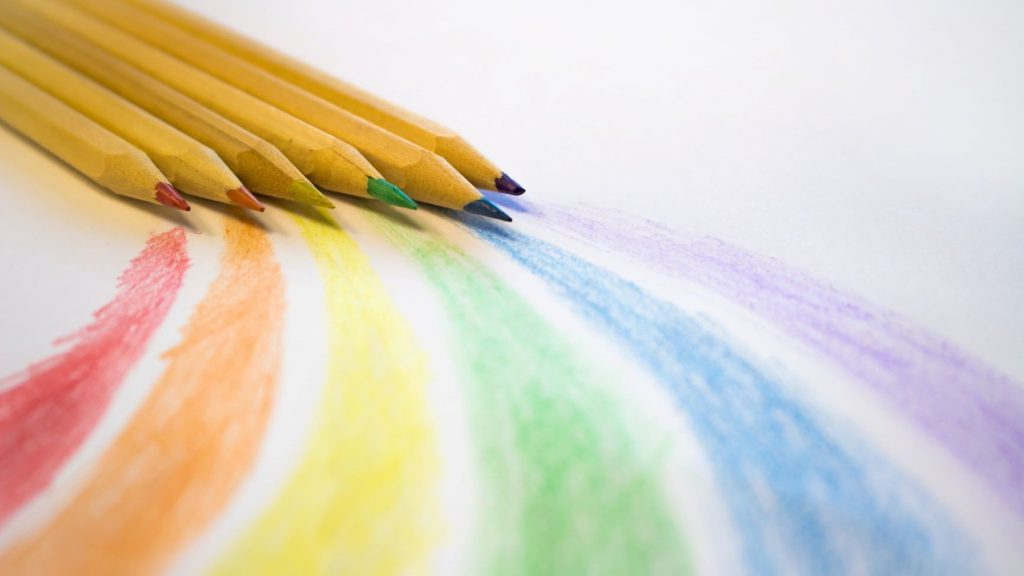 six brown colored pencils drawing a rainbow