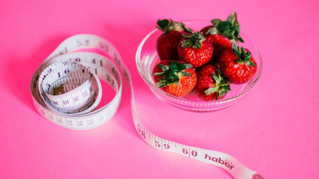 measuring tape and a bowl of strawberries on a bright pink background
