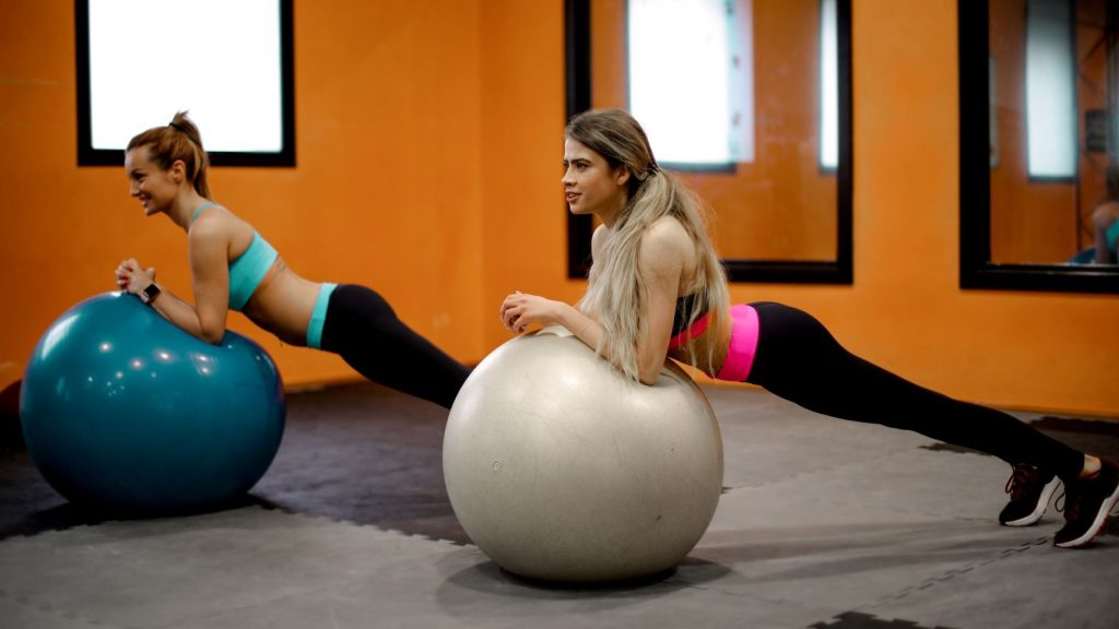 women exercising on fitness balls in a gym