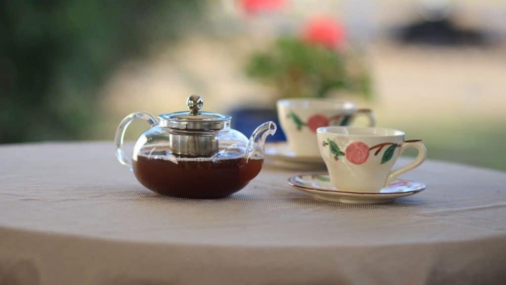 clear tea pot with tea cups