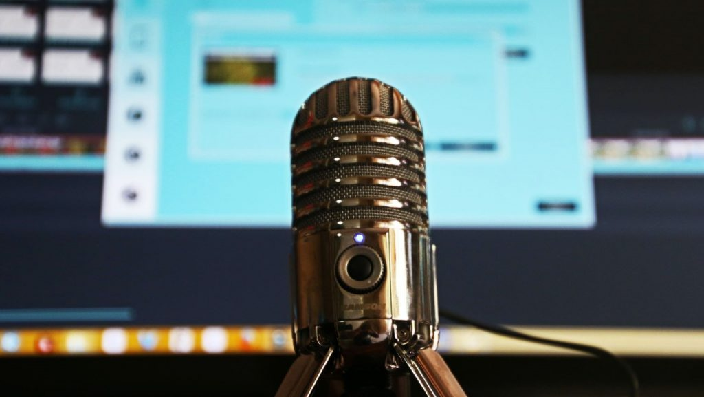 podcast microphone in front of laptop screen