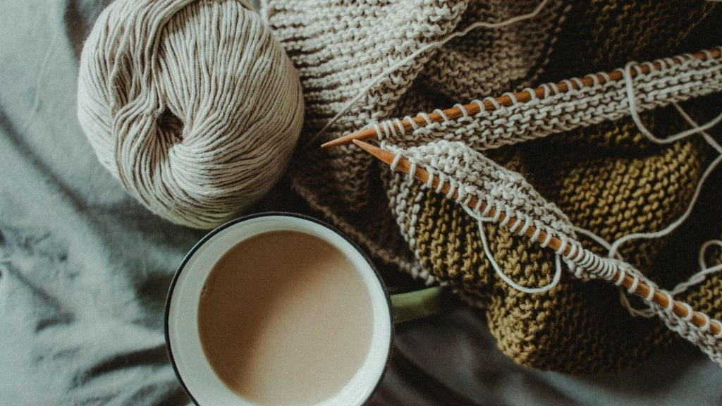coffee mug next to knitting needles
