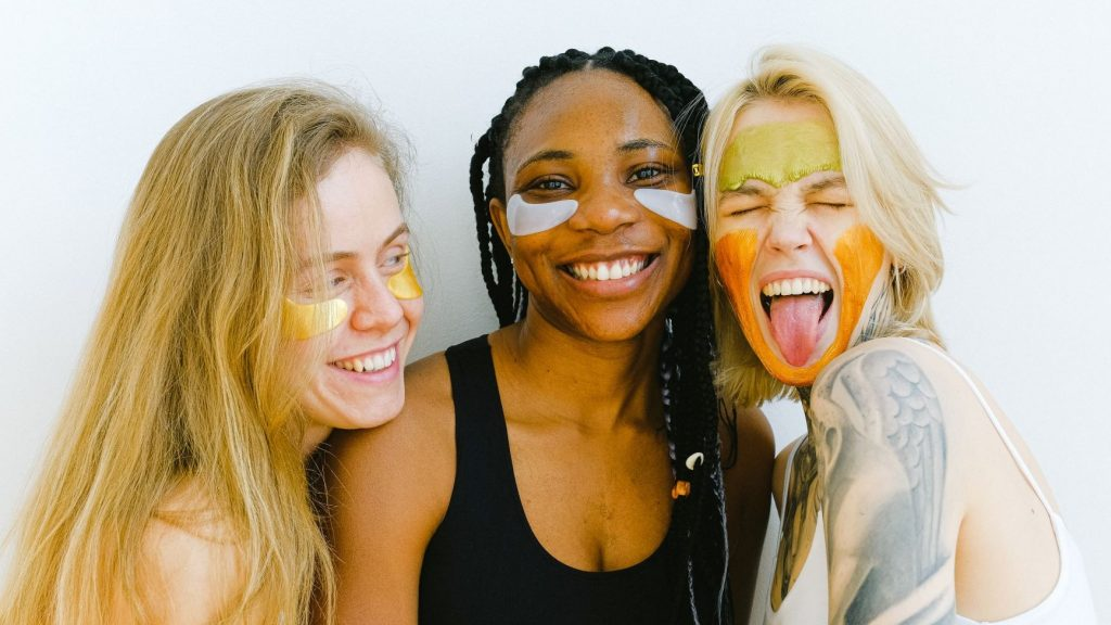 three women wearing skincare products